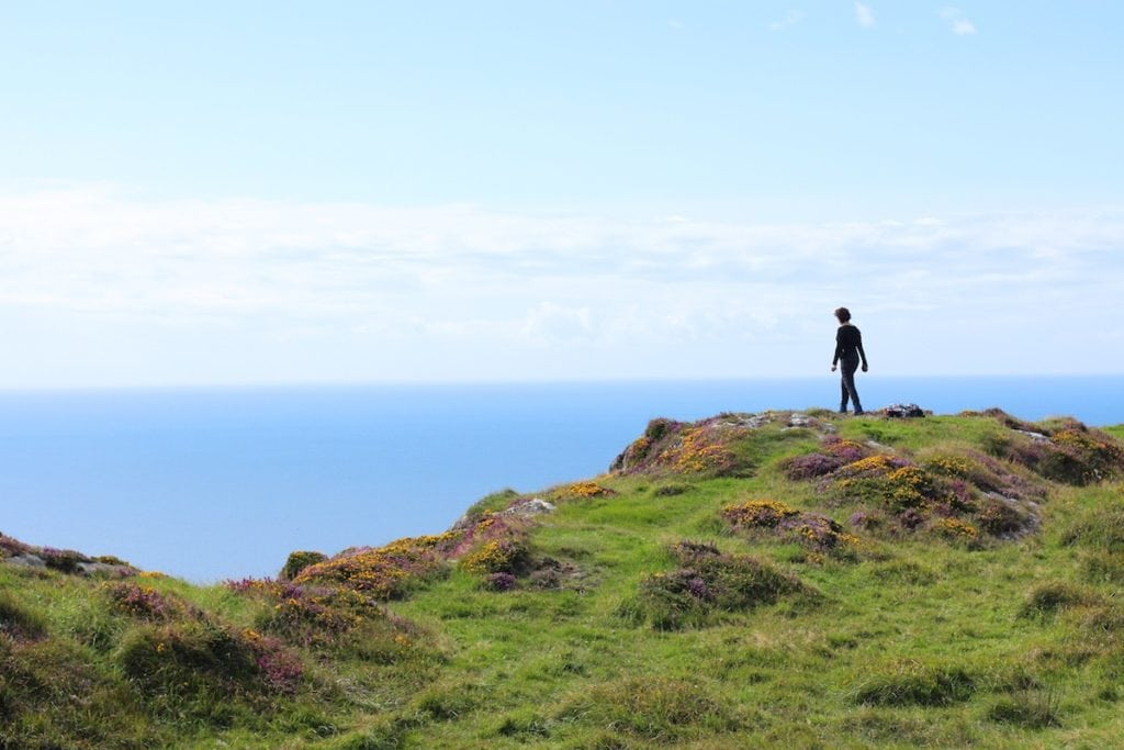A picture of a woman on a beautiful Irish landscape near the sea